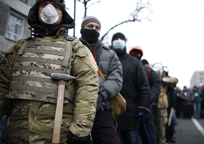 People wear masks as they attend a rally held by supporters of EU integration in Kiev