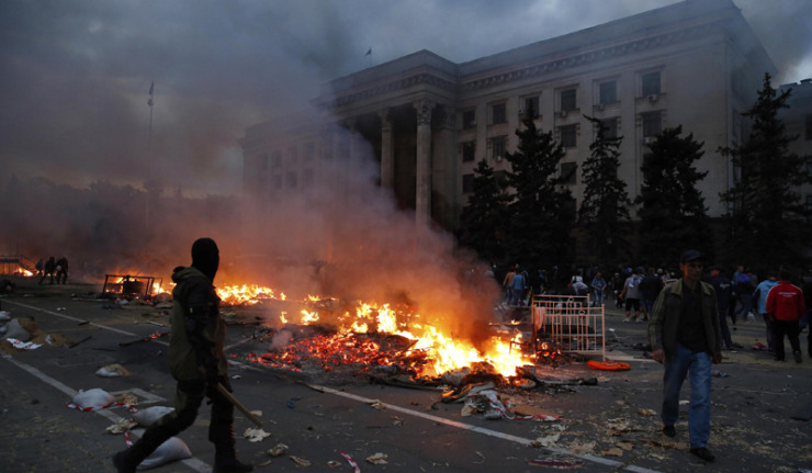 A protester walks past a burning pro-Russian tent camp near the trade union building in Odessa